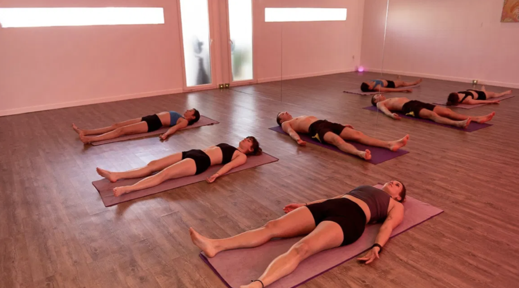 Women and a men are practicing hot yoga.