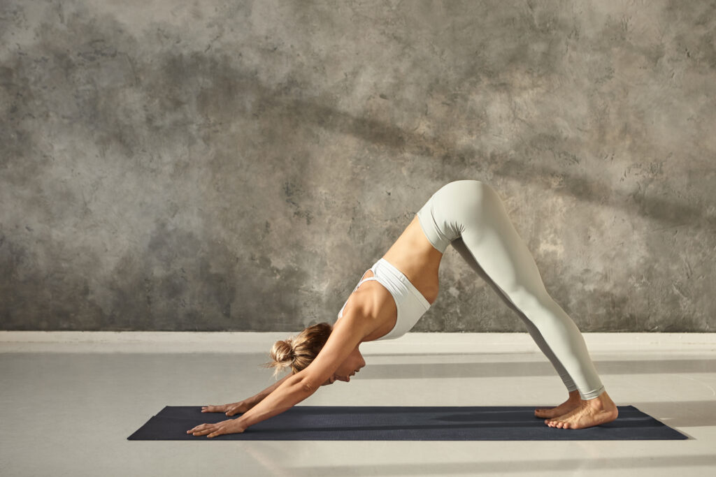 Full length side view of beautiful young fit woman in sportswear working out indoors, practicing vinyasa yoga exercise on mat