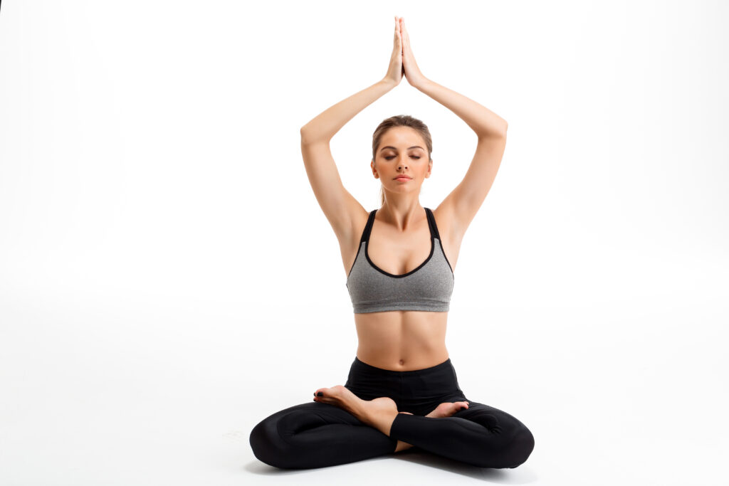 Portrait of young beautiful sportive girl is doing kundalini yoga pose over white background.