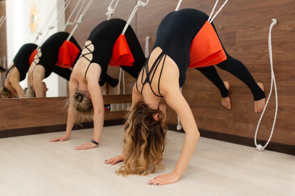 Women practicing iyengar yoga on ropes stretching in gym