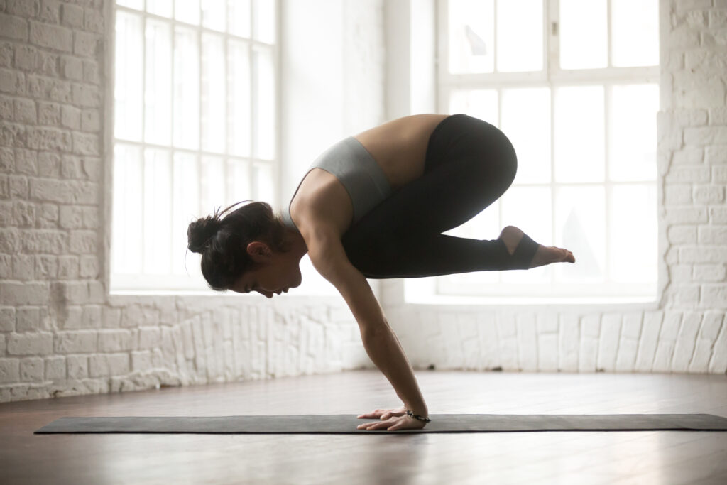 Young attractive woman is doing ashtanga in Crane pose, white loft studio backgrou
