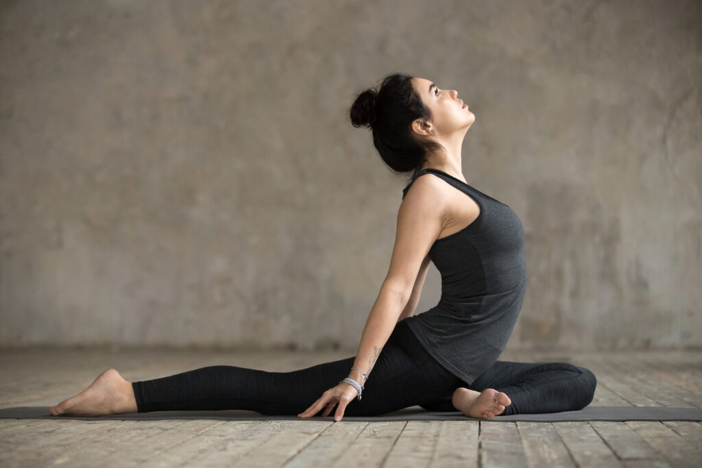Young woman is doing hatha yoga with single pigeon pose