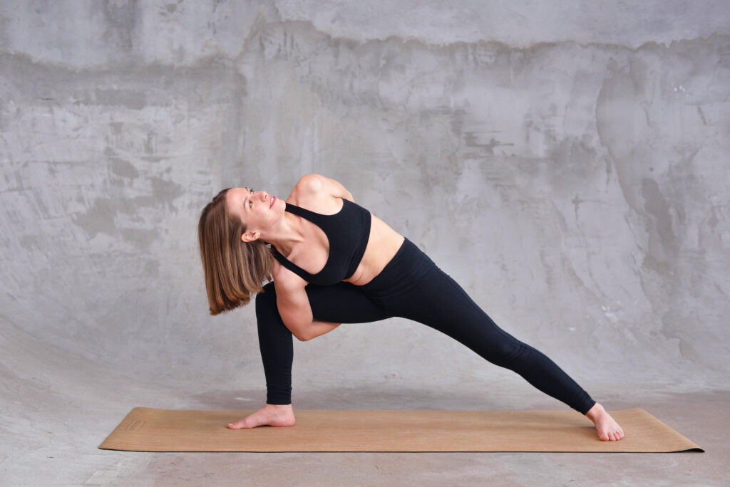 Young woman wearing black sportswear practicing bikram yoga, doing Utthita parsvakonasana exercise on mat, standing in Extended Side Angle pose, beautiful girl working out at home or in yoga studio.